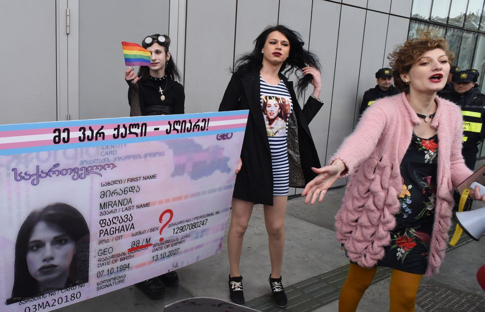 Supporters of Georgia's LGBTQ community hold the giant identity card of transgender Miranda Paghava, who is demanding the cha