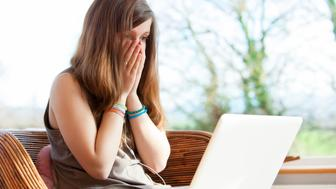 Teenage girl with hands on face victim of cyber bullying