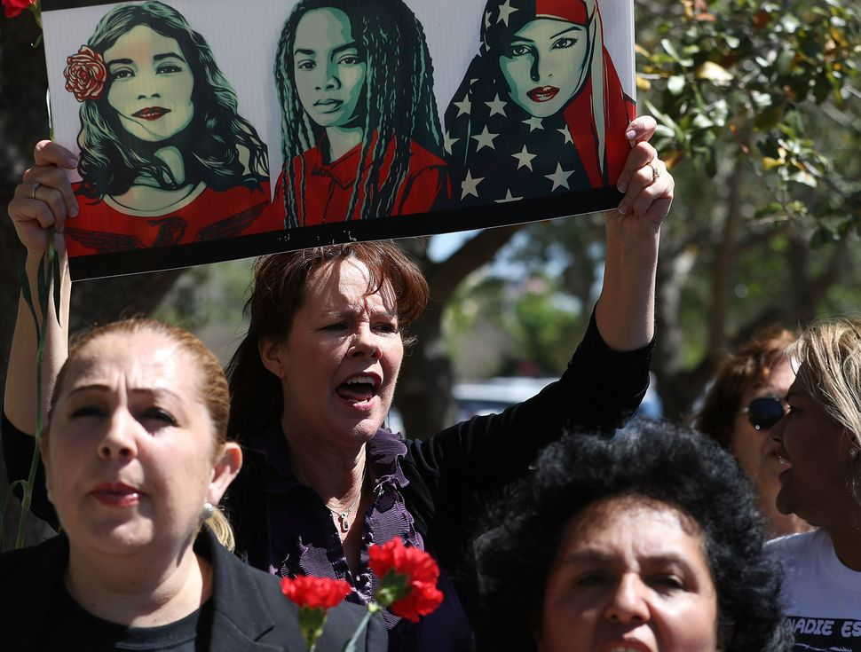 Laurie Woodward Garcia, center, joins other women on International Women's Day in front ofa U.S. Department of Homeland