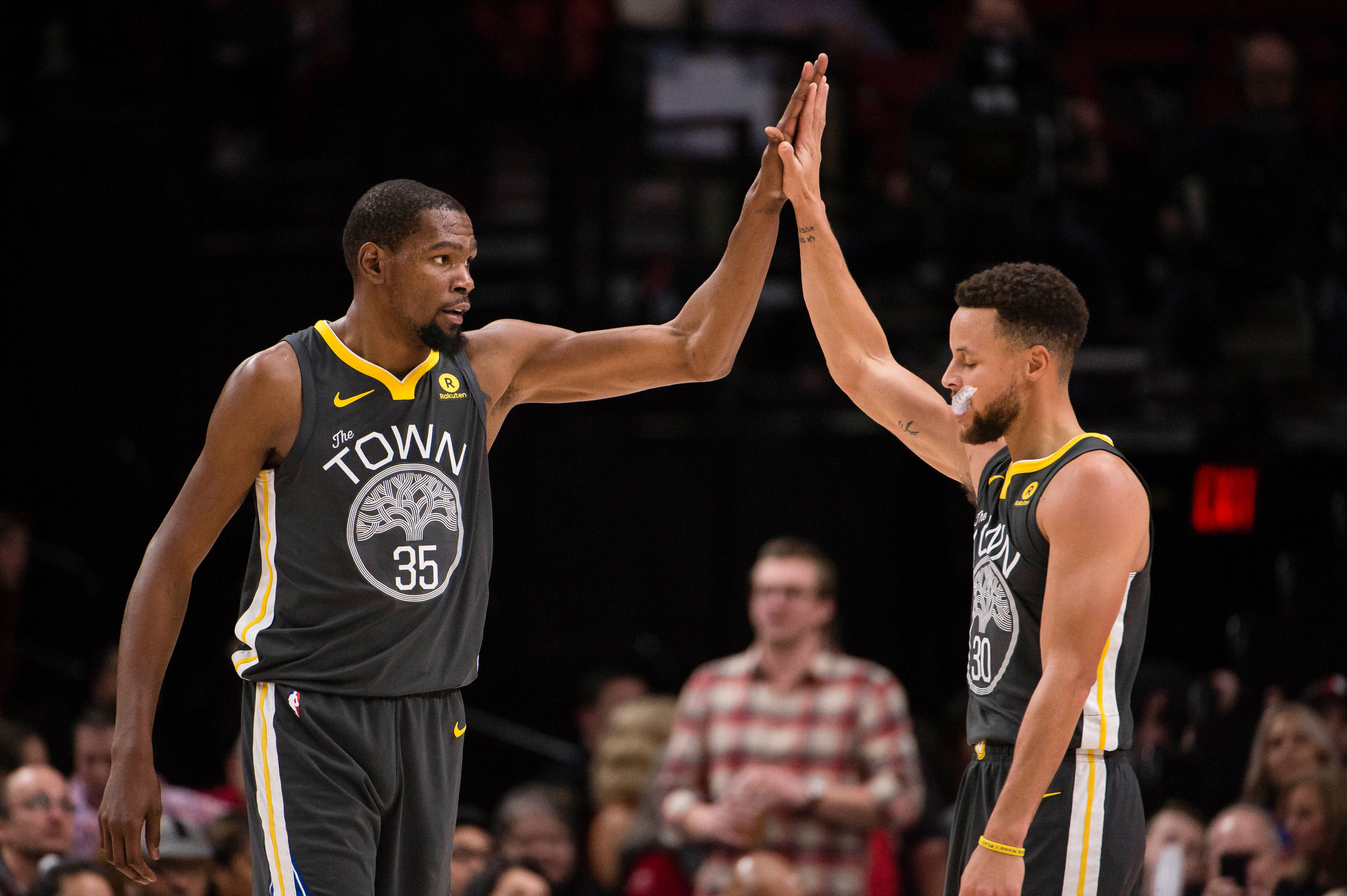 Feb 14, 2018; Portland, OR, USA; Golden State Warriors forward Kevin Durant (35) high-fives guard Stephen Curry (30) during the second half in a game agains the Portland Trail Blazers at the Moda Center. The Trail Blazers won 123-117. Mandatory Credit: Troy Wayrynen-USA TODAY Sports