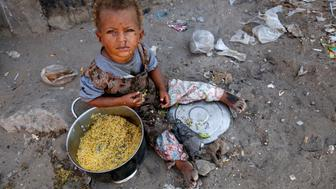 A girl displaced by the war in the northwestern areas of Yemen eats outside her family's makeshift hut on a street in the Red Sea port city of Hodeida, Yemen December 25, 2017. REUTERS/Abduljabbar Zeyad