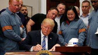 U.S. President Donald Trump signs a presidential proclamation placing tariffs on steel and aluminum imports while surrounded by workers from the steel and aluminum industries at the White House in Washington, U.S. March 8, 2018. REUTERS/Leah Millis