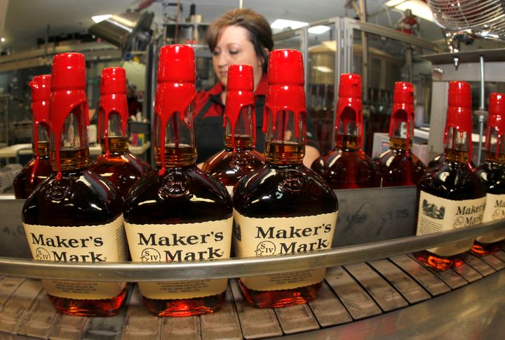New bottles of Maker's Mark bourbon on the conveyor belt pass by a worker after being hand dipped with their signature red wa