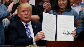 U.S. President Donald Trump holds up a proclamation during a White House ceremony to establish tariffs on imports of steel and aluminum at the White House in Washington, U.S., March 8, 2018. REUTERS/Leah Millis