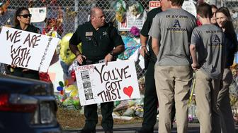 PARKLAND, FL - FEBRUARY 28:  Broward County Sheriff officers welcome students as they arrive at Marjory Stoneman Douglas High School as students arrive to attend classes for the first time since the shooting that killed 17 people on February 14  at the school on February 28, 2018 in Parkland, Florida.  Police arrested 19-year-old former student Nikolas Cruz for the 17 murders.  (Photo by Joe Raedle/Getty Images)