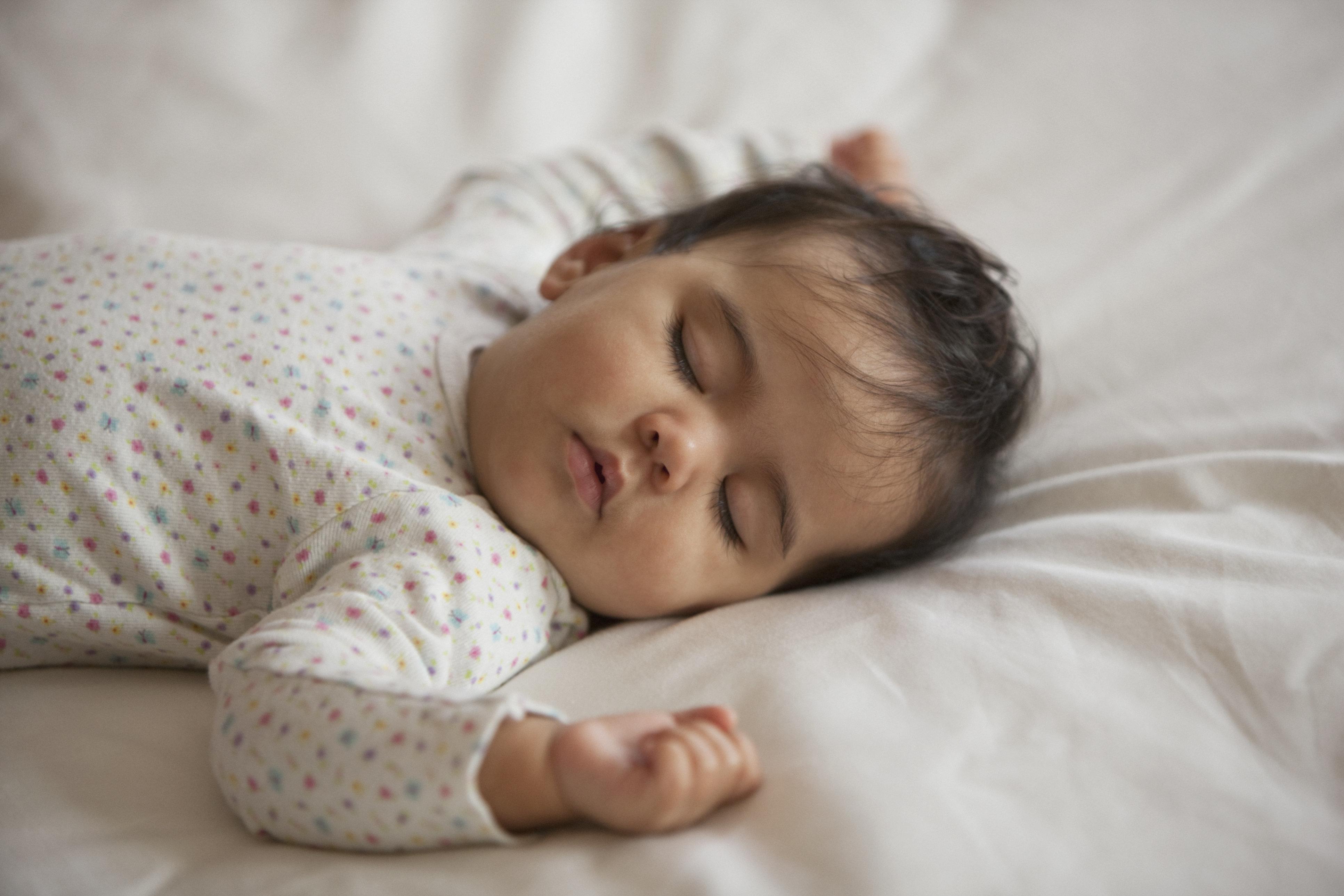 Mixed race baby girl sleeping on bed