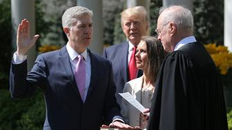 Judge Neil Gorsuch (L) is sworn in as an associate justice of the Supreme Court by Supreme Court Associate Justice Anthony Kennedy (R) , as U.S. President Donald J. Trump (C) watches with Louise Gorsuch in the Rose Garden of the White House in Washington, U.S., April 10, 2017. REUTERS/Carlos Barria