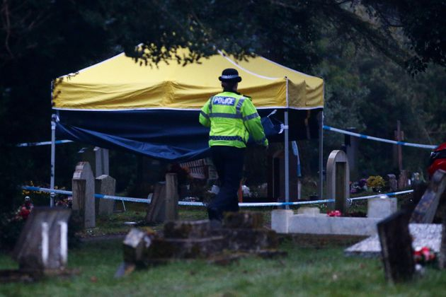A police officer walks past a forensics tent over the grave of former Russian double agent Sergei Skripal's wife Lyudmila