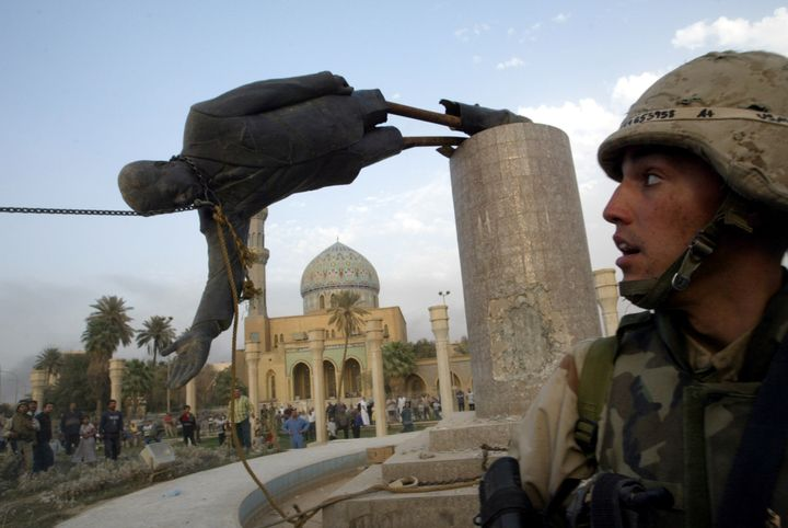 A U.S. soldier watches as a statue of Iraq's President Saddam Hussein falls in central Baghdad, Iraq, April 9, 2003.