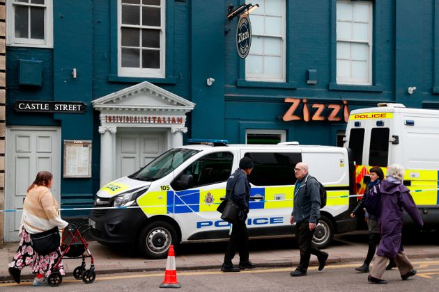 Pedestrians walk past a cordoned-off branch of the Italian chain restaurant Zizzi close to The Maltings shopping centre in Salisbury