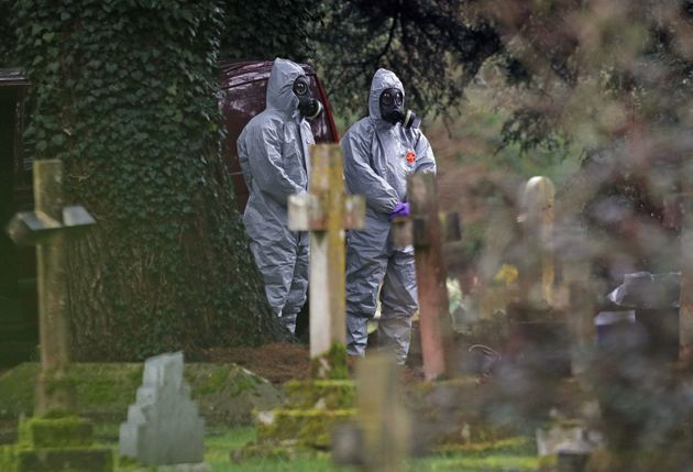 Forensic officers in gas masks at the London Road cemetery in Salisbury, Wiltshire.