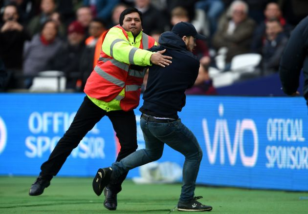 A pitch invader is confronted by security during the Premier League match at the London