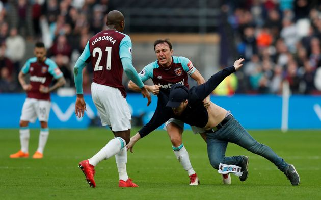 West Ham United's Mark Noble clashes with a fan who has invaded the