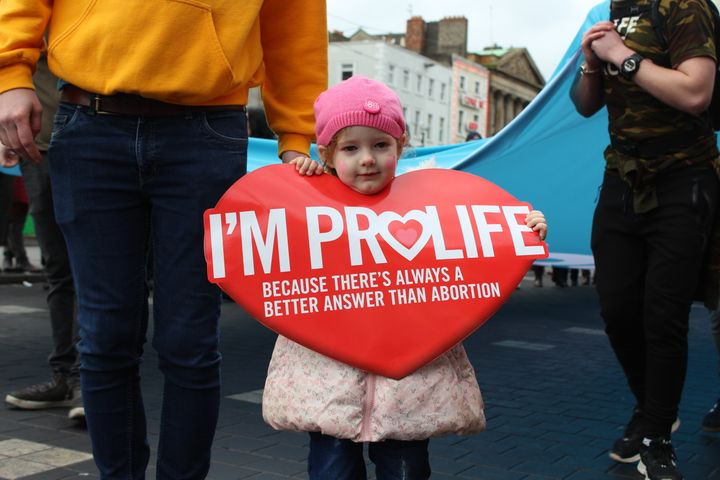 A little girl holds up a sign at an anti-abortion rally.