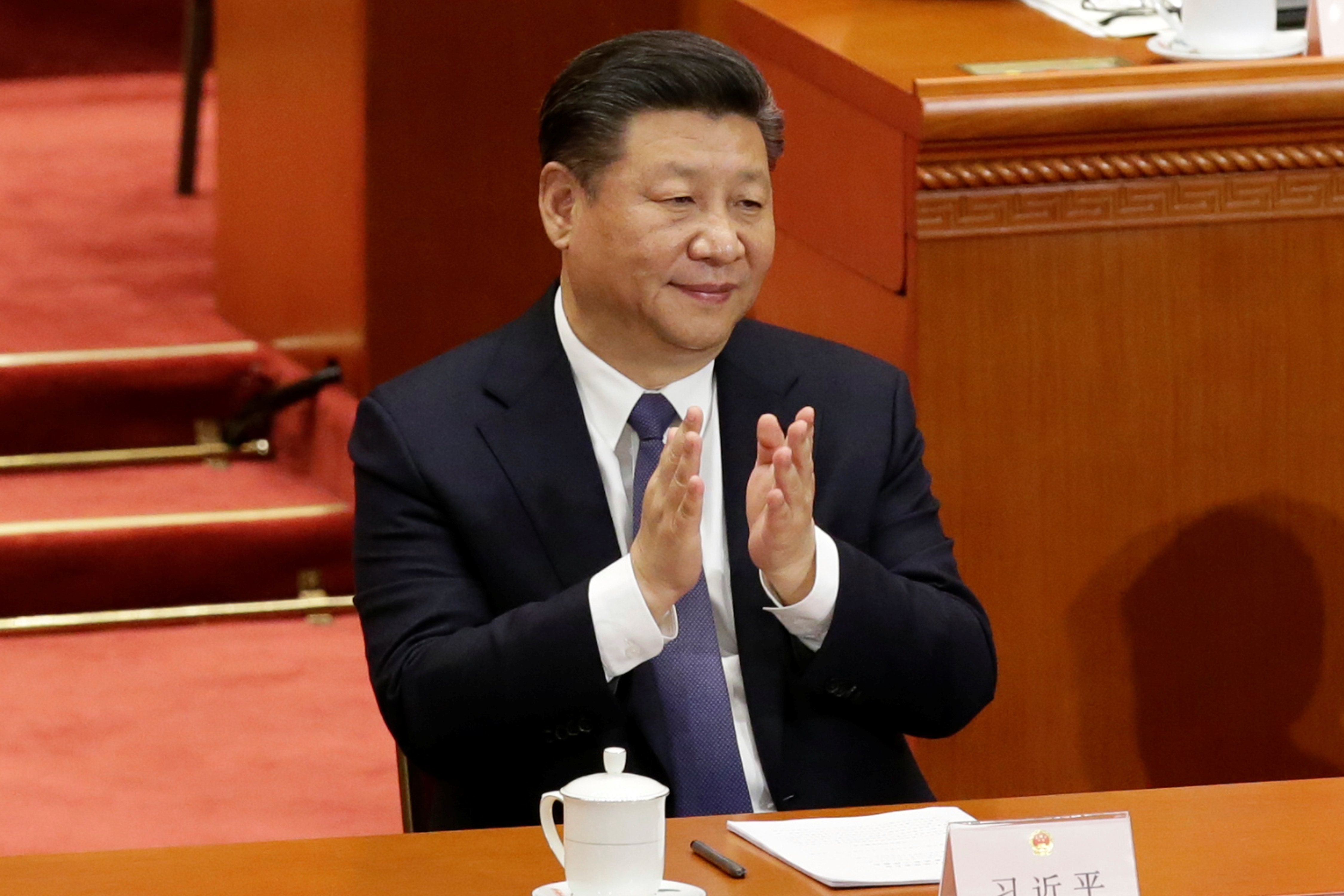 Chinese President Xi Jinping applauds after the parliament passed a constitutional amendment lifting presidential term limit, at the third plenary session of the National People's Congress (NPC) at the Great Hall of the People in Beijing, China March 11, 2018.  REUTERS/Jason Lee