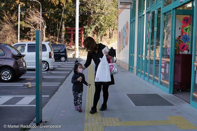 2011년 4월 후쿠시마현, 사고 현장에서 70km가량 떨어진 코리야마시의 식품 매장 앞에서 장을 보고 나오는 엄마와 딸. 그린피스는 이 지역에서 식품과 토양의 방사성 오염을 조사