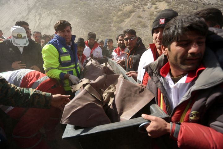 Medics and rescuers evacuate the body of a victim killed in a private plane crash in Iran, March 12, 2018. The crash killed 1