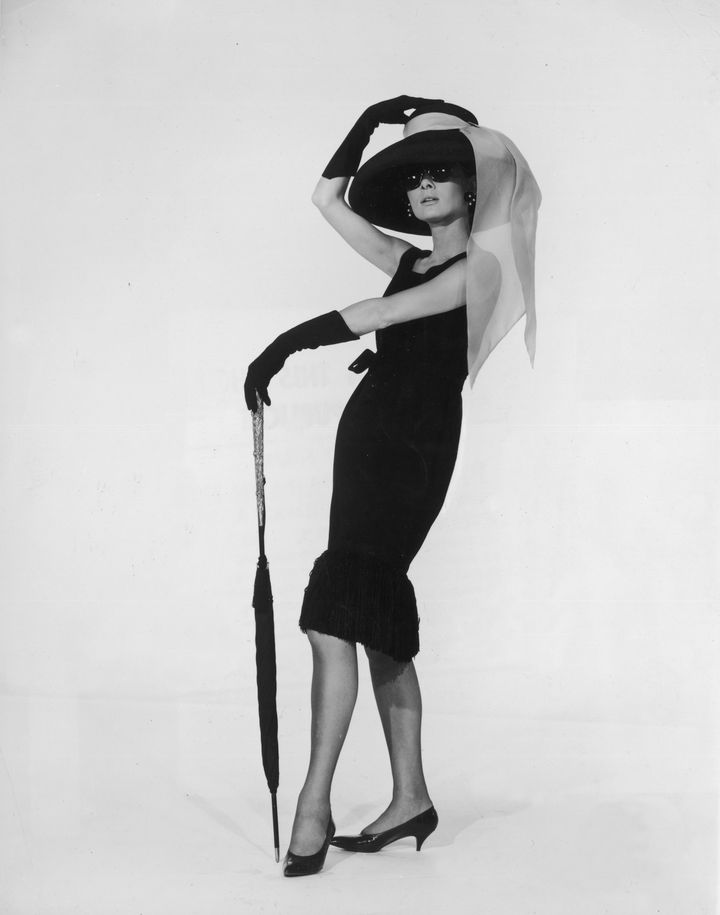 Actress Audrey Hepburn wears the black cocktail dress designed by French couturier Hubert de Givenchy in a promotional p