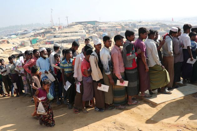 Rohingya refugees stand in a queue to collect aid supplies in Kutupalong refugee camp in Cox's Bazar,...