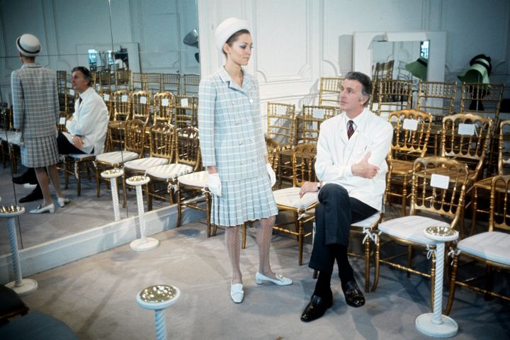 Hubert de Givenchy with a model wearing his design in 1969.
