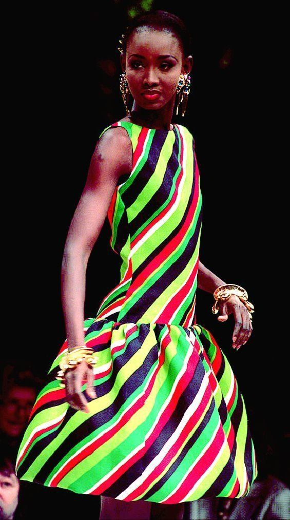 A model presents a short bouffant red, green, black and white striped sleeveless cocktail dress by Givenchy during his 1993&n