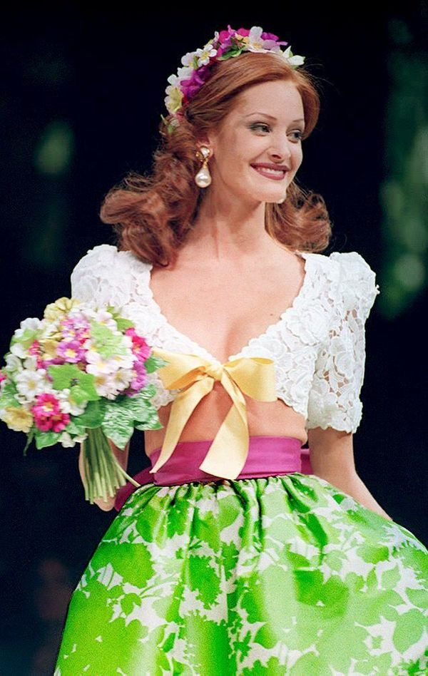 A model presents a wedding dress, a white guipure lace bolero with a green and white faille skirt, at the end of the Giv
