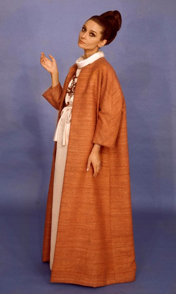 Hepburn wearing a Givenchy burnt orange raw silk and shantung floor-length coat over an off-white floor length dress with tie