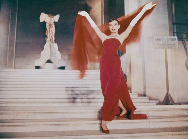 "Hepburn wearing a red dress by Givenchy in a scene from the film ""Funny Face"" in 1957."
