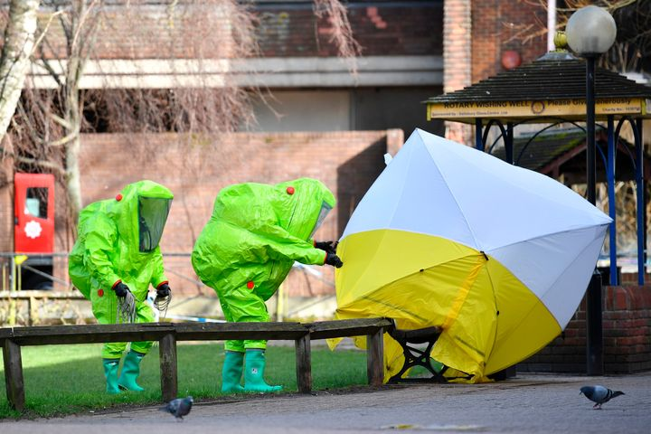 Members of emergency services in green biohazard encapsulated suits fix a tent over the bench where Sergei Skripal and h