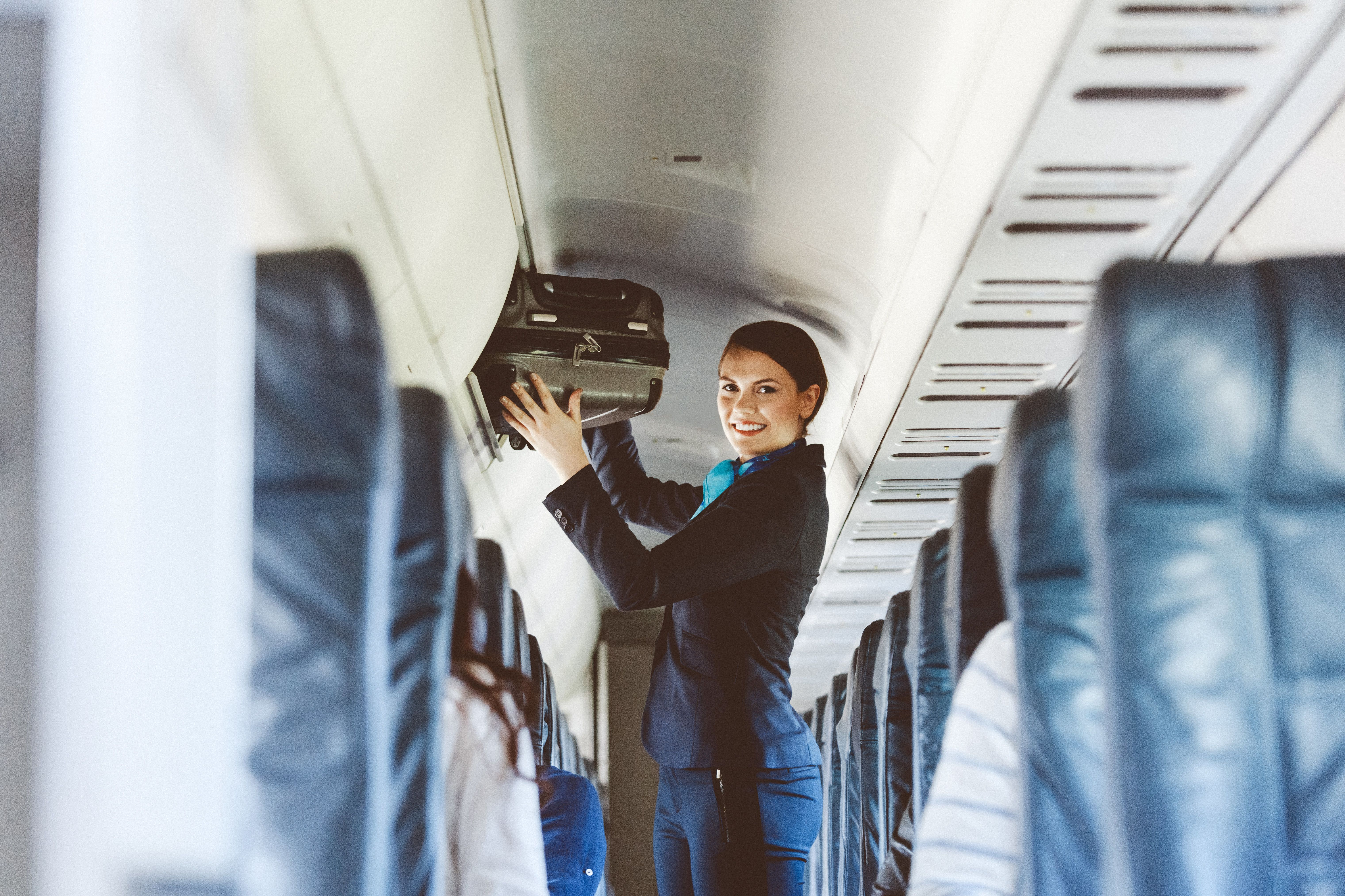 Beautiful air stewardess inside an airplane holding suitcase, smiling at the camera.