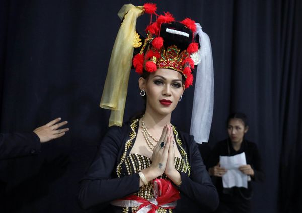 Contestant Juana Paing of Myanmar prepares to go on stage with a traditional headdress.