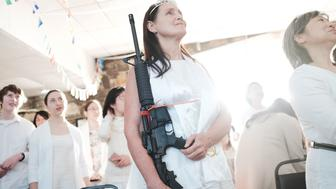 NEWFOUNDLAND, PA - FEBRUARY 28:  A woman holds an AR-15 rifle during a ceremony at the World Peace and Unification Sanctuary on February 28, 2018 in Newfoundland, Pennsylvania. The controversial church, which is led by the son of the late Rev. Sun Myung Moon, believes the AR-15 symbolizes the 'rod of iron' in the biblical book of Revelation, and it has encouraged couples to bring the weapons to a 'commitment ceremony' or 'Perfection Stage Book of Life Registration Blessing'. Officials in the rural area in the Pocono Mountains have reportedly told elementary school parents that their children will be relocated on Wednesday to accommodate the AR-15 ceremony. The semiautomatic rifles are similar to the weapon used in a Florida high school shooting on February 14.  (Photo by Spencer Platt/Getty Images)