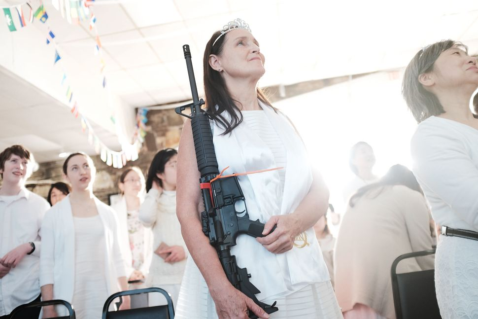 A woman holds an AR-15 rifle during a ceremony at the World Peace and Unification Sanctuary on Feb. 28 in Newfoundland,