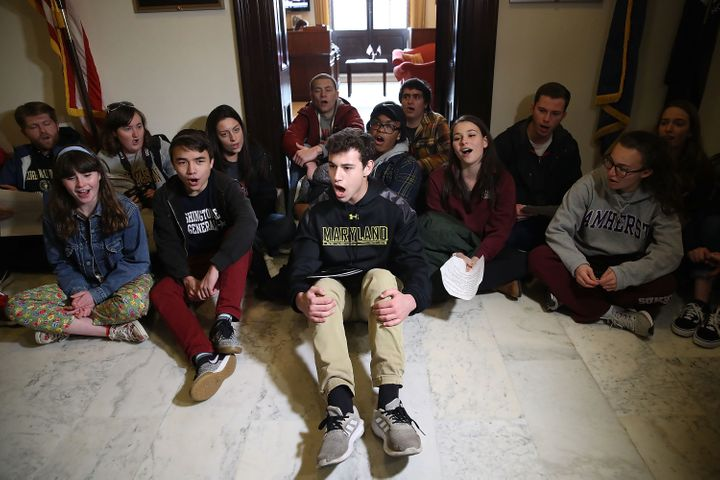 Students sit and protest in front of Senate Majority Leader Mitch McConnell's office in Washington, D.C., to urge Congress to