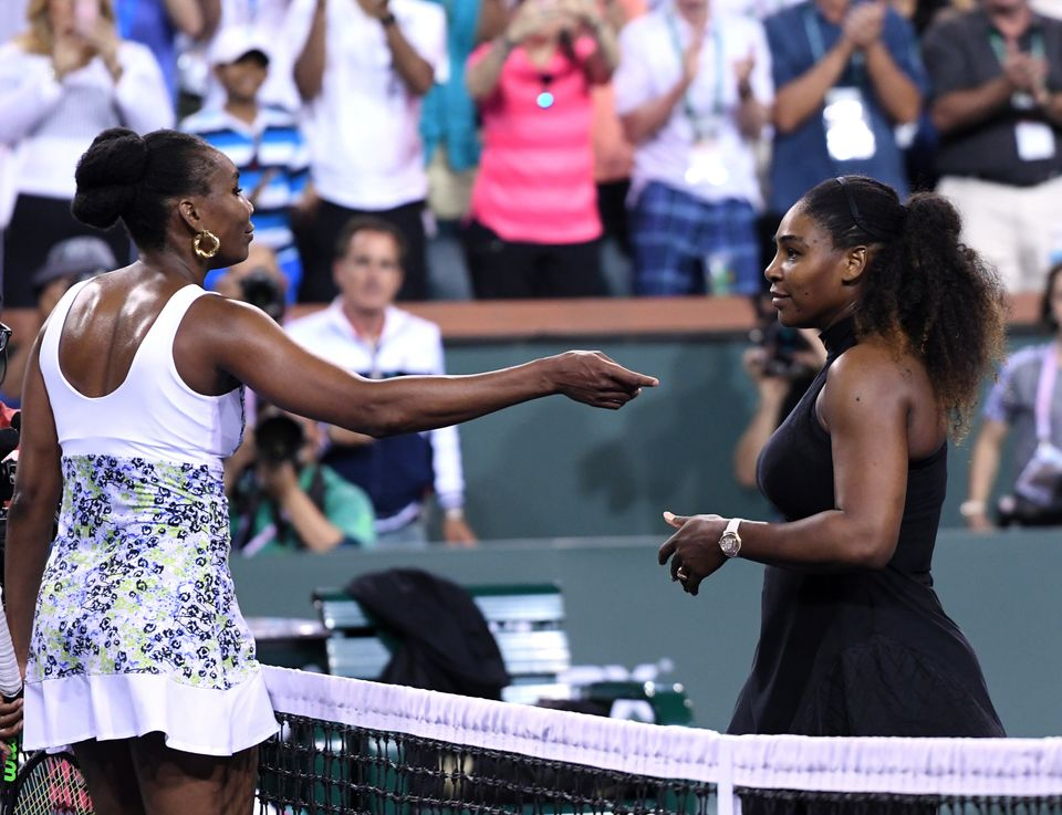 Venus Williams (L) hugs Serena Williams after her win over her sister during Day 8 of BNP Paribas Open...