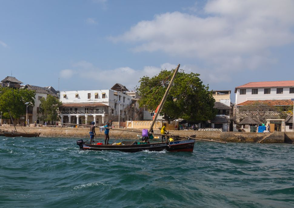 A dhow is guided in from the old town in Lamu, Kenya. The town may soon be the site of the country's first coal pla