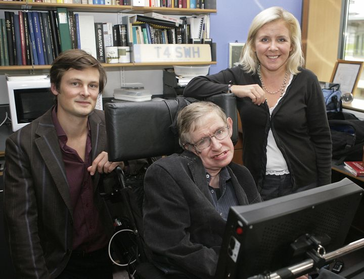Professor Stephen Hawking, (C) his daughter Lucy (R) and Christophe Galfard pose for photographs in Professor Hawking's office at The Centre for Mathematical Sciences in Cambridge, in central England, 03 September 2007.