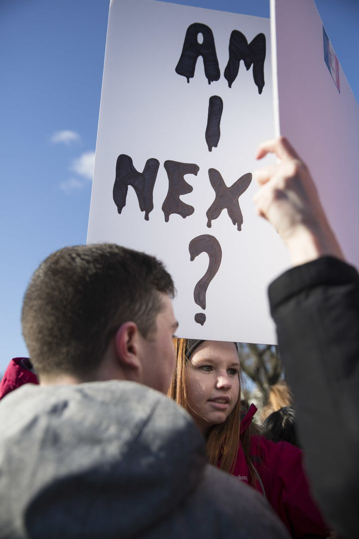 A student holds a sign reading 'Am I Next?' outside the White House on Wednesday.