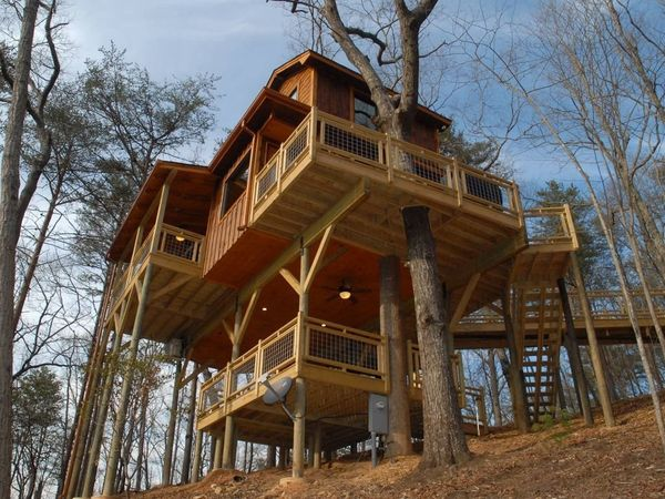 This upscale treehouse includes a fire pit, hot tub, and even a hanging bed that make it feel like a true getaway. Located of