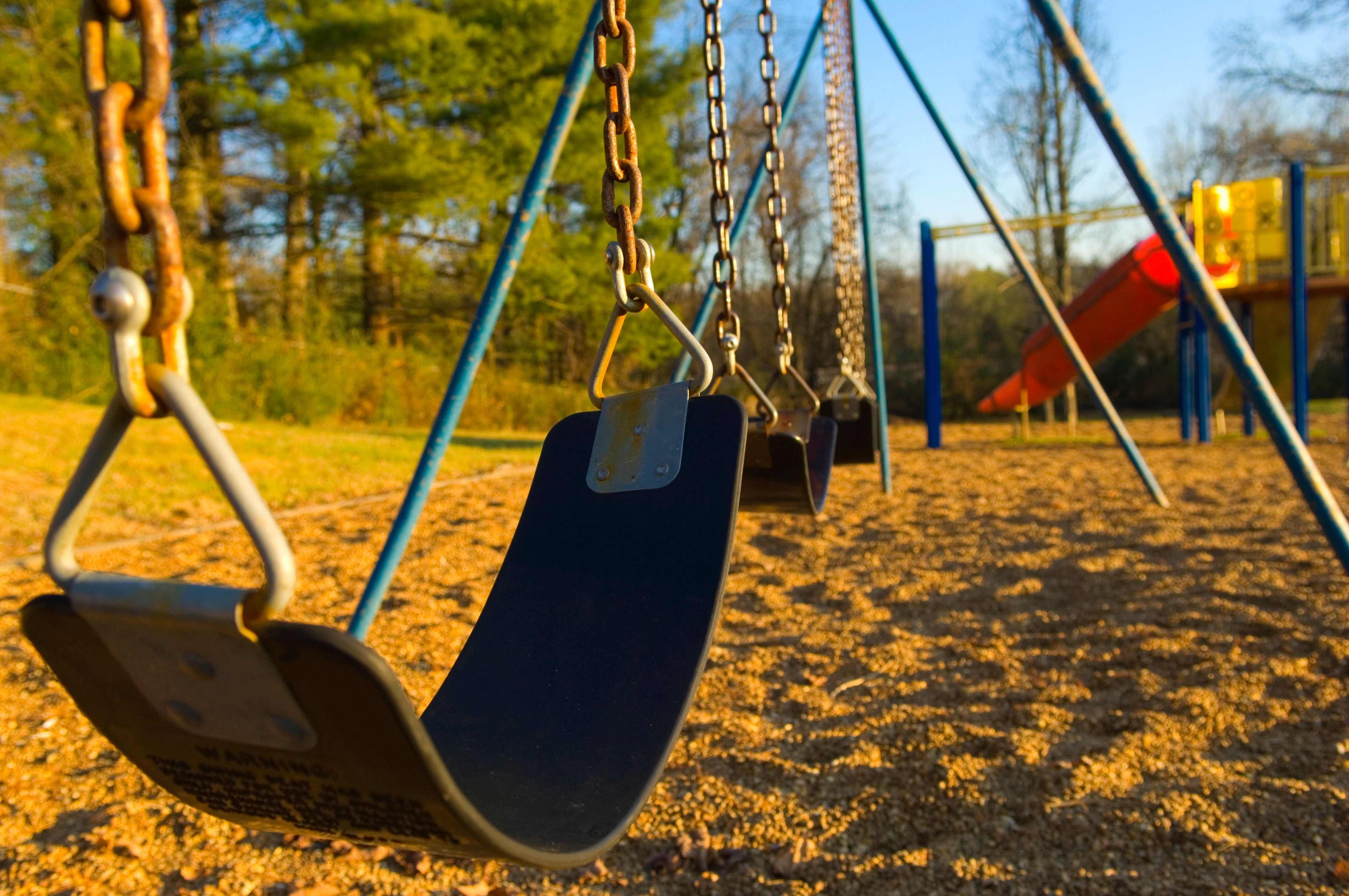 A color image of a child's swing-set at a playground at a local school or park. the photo is a close up of the seat for the swings with a child's slide, monkey bars and playground in the background at a local school or park. there are also trees with green leaves and blue sky in the background. the swings are connected to metal chains that the children swing on during playtime while at school. and the lighting is sunlight during the day.    more playground pictures: click here [url=http://www.istockphoto.com/file_search.php?action=file&lightboxID=4651500][img]http://www.istockphoto.com/file_thumbview_approve.php?size=1&id=5073108[/img][/url]