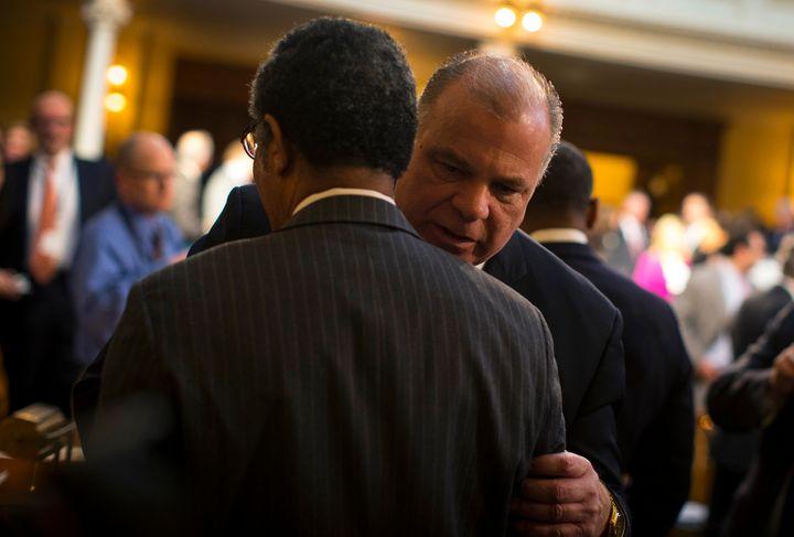New Jersey state Senate President Stephen Sweeneygrabs hold ofa colleague on the floor of the legislative chamber