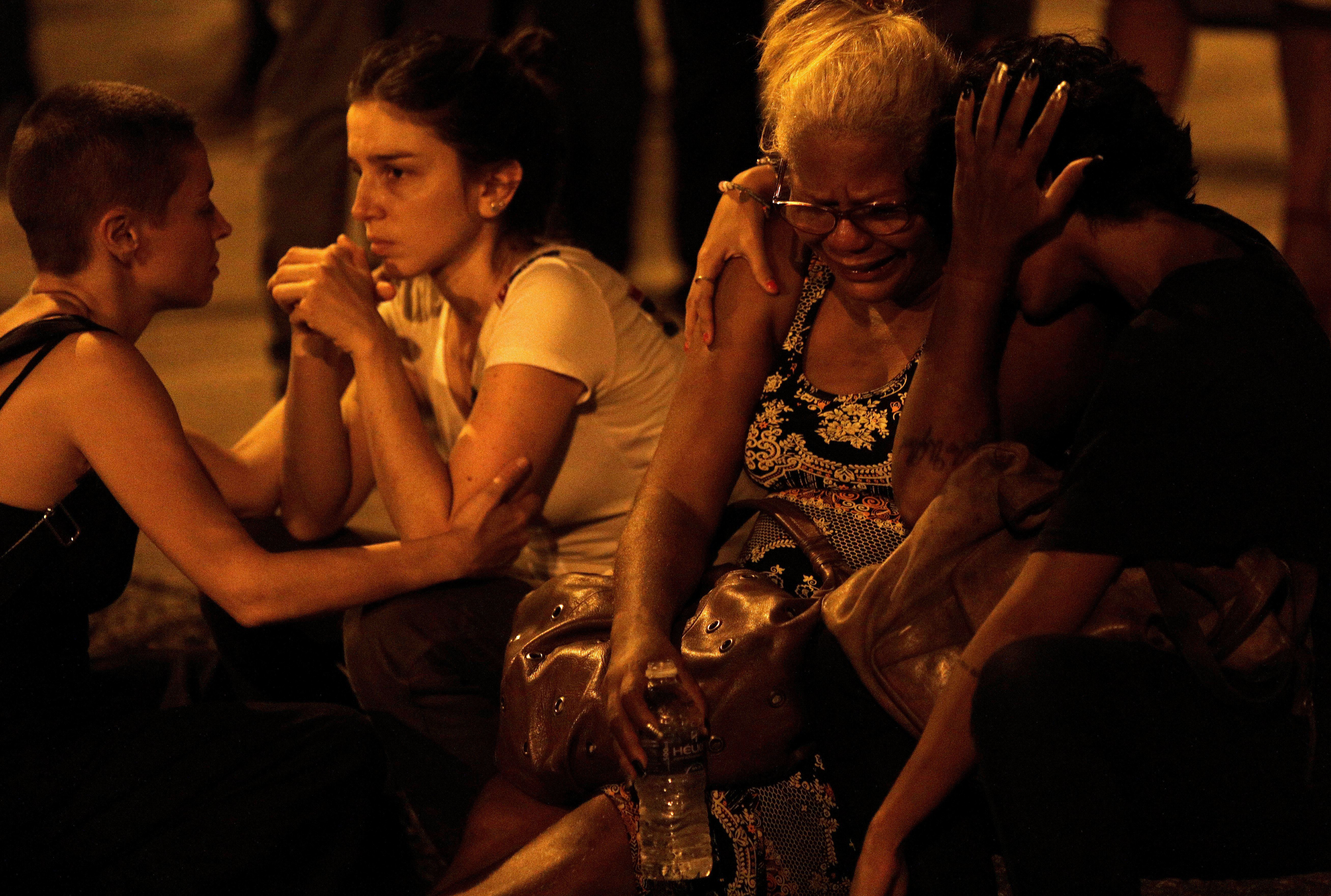 Women react next to the crime scene where Rio de Janeiro city councilor Marielle Franco was shot dead in Rio de Janeiro, Brazil March 15, 2018.  REUTERS/Ricardo Moraes