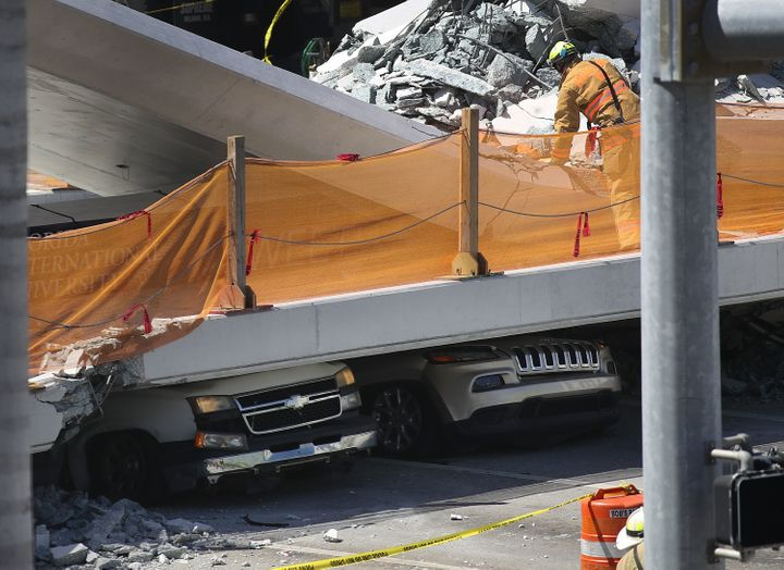 Vehicles are trapped under the collapsed pedestrian bridgeon March 15.