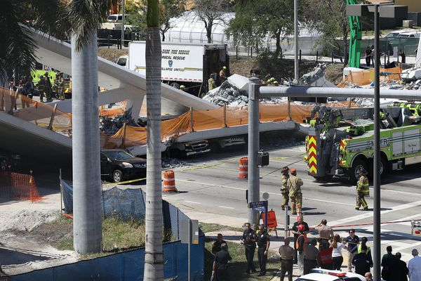 Vehicles are seen trapped under the collapsed bridge.