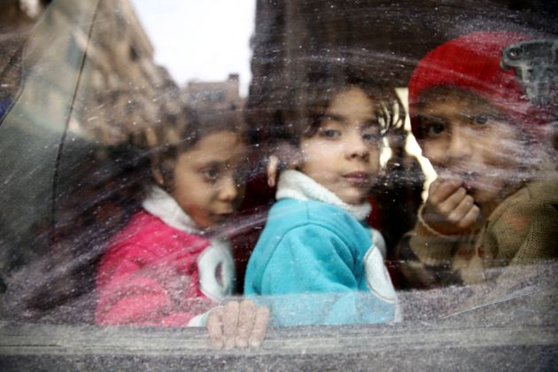 Children look through a bus window during an evacuation from the besieged town of Douma, in Syria's eastern...