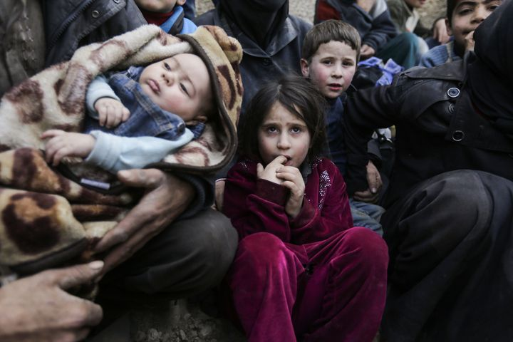 Syrian children wait to be evacuated from the eastern Ghouta enclave on the outskirts of Damascus on March 15, 2018.