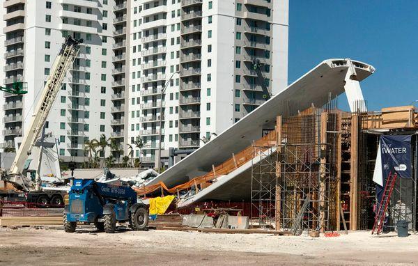 A crane is seen nearthe collapsed pedestrian bridge.