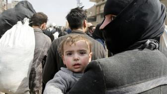 A Syrian woman carrying a child evacuated from the Eastern Ghouta enclave walks pass with other civilians through the regime-controlled corridor opened by government forces in Hawsh al-Ashaari, east of the enclave town of Hamouria on the outskirts of the capital Damascus on March 15, 2018. Thousands escaped Syria's rebel-held Eastern Ghouta into government-held territory AFP correspondents on both sides said, the largest numbers since the regime assault on the enclave began. / AFP PHOTO / LOUAI BESHARA        (Photo credit should read LOUAI BESHARA/AFP/Getty Images)