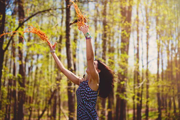 한 여성이 숲에서 공중에 스파게티 면을 던지는