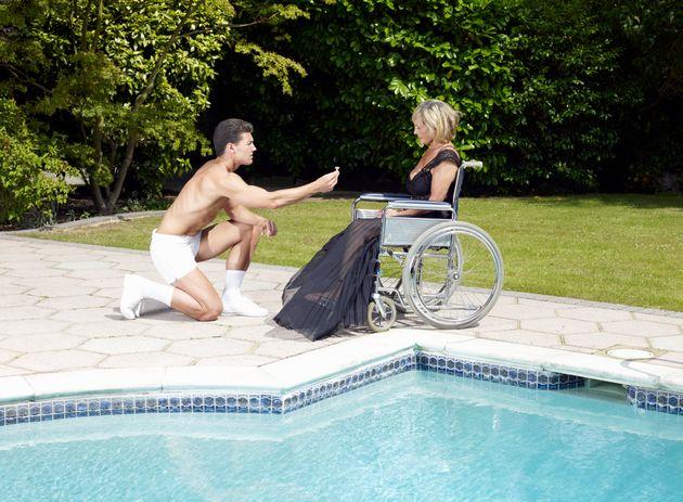 젊은 남성이 휠체어를 탄 중년 여성에게 프로포즈를 하고 있다. 바로 옆에는 수영장이